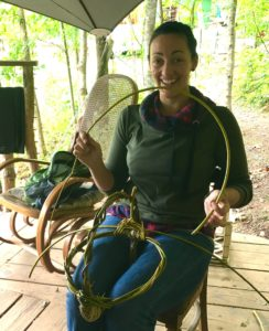 permaculture apprentice making a willow basket